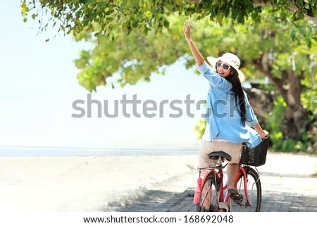 carefree woman having fun riding bicycle and raised her arm at the beach - stock photo