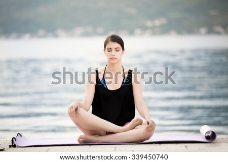 Carefree woman meditating.Vacation vitality healthy living.Free woman embracing the sunshine,enjoying peace,serenity in nature.Beautiful fit female fitness woman practicing yoga.Summer body goals - stock photo