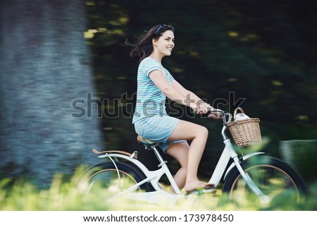 Carefree woman riding bicycle in park having fun on summer afternoon - stock photo