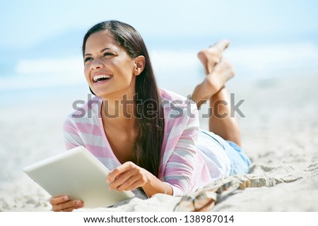 carefree woman uses touchpad tablet technology on the beach with internet vacation - stock photo