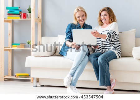 Carefree woman using computer with parent - stock photo