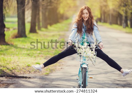 Carefree woman with bicycle riding in park having fun and smiling - stock photo