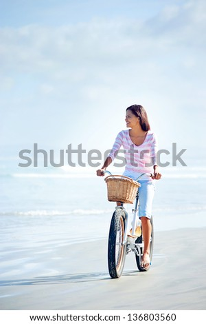 carefree woman with bicycle riding on beach sand having fun and smiling - stock photo