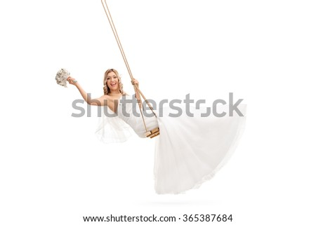 Carefree young bride swinging on a wooden swing and holding a wedding flower isolated on white background