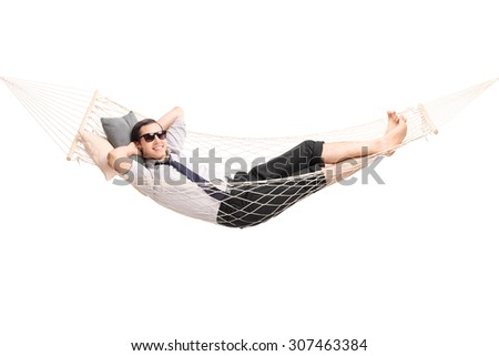 Carefree young businessman lying in a hammock and looking at the camera isolated on white background