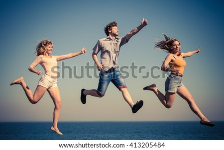 Carefree young friends people jumping by sea ocean water. Happy women and man having fun. Summer happiness and freedom.