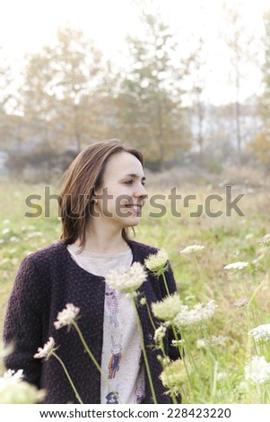 carefree young girl with coat smiling in a wildflowers field with sunlight - stock photo