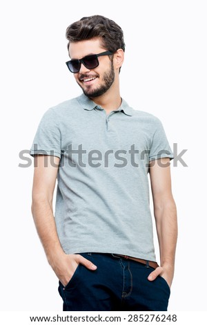 Carefree young man. Happy young man holding hands in pockets and smiling while standing against white background