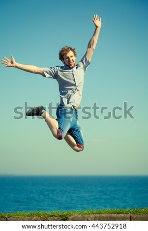 Carefree young man jumping by sea ocean water. Happy guy having fun. Summer happiness and freedom.