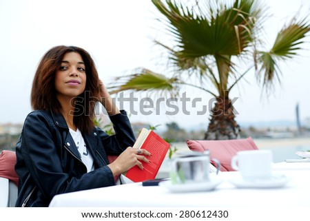 Carefree young woman enjoying a good day with book while sitting at sidewalk cafe near the beach, attractive afro american woman looking for someone in restaurant - stock photo