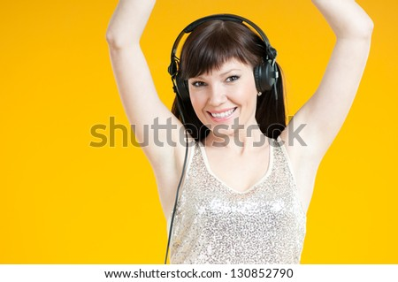 Carefree young woman listening to music in headphones and dancing, yellow background - stock photo
