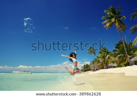 Carefree young woman playing with the clear water on exotic beach - stock photo