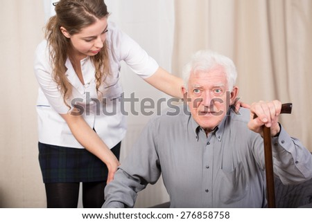 Careful female caregiver helping older man to stand up - stock photo