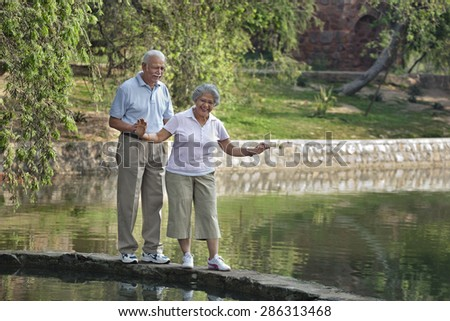 Careful mature woman balancing while walking with man in park - stock photo