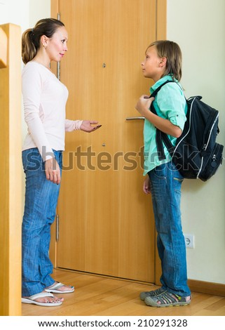 Careful mother gives moral admonitions to teenager son at doorway - stock photo