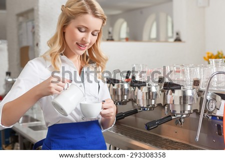 Careful work. Young pretty female barista standing in coffee shop and pouring some milk in cup. - stock photo