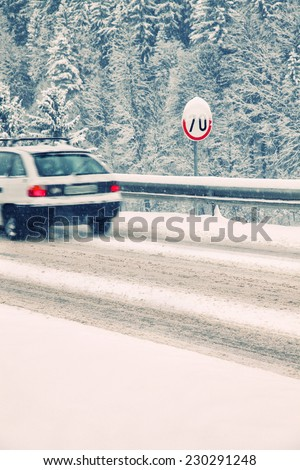 Carefully driving of a vehicle on the heavy snow road with speed limit table.. Motion blur (long time exposure) visualizies the speed and dynamics. - stock photo