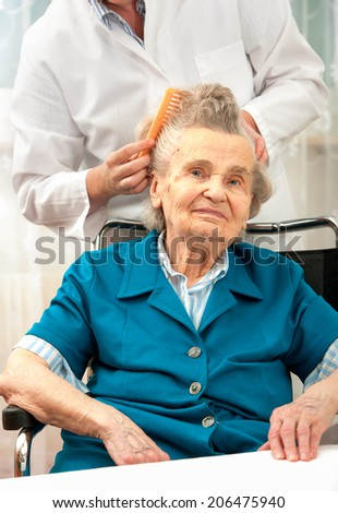 Caregiver dressing the hair of a senior woman. Home help - stock photo