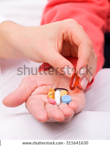 Caregiver giving medication to her senior patient - stock photo