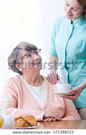 Caregiver giving senior woman coffee and croissant
