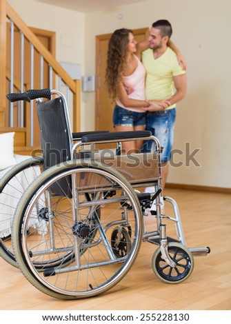 Caregiver helps handicapped girl to ambulate without invalid  chair. Focus on wheelchair - stock photo