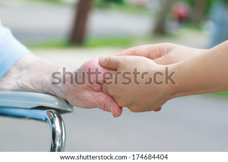 Caregiver holding an elderly woman's hand outside