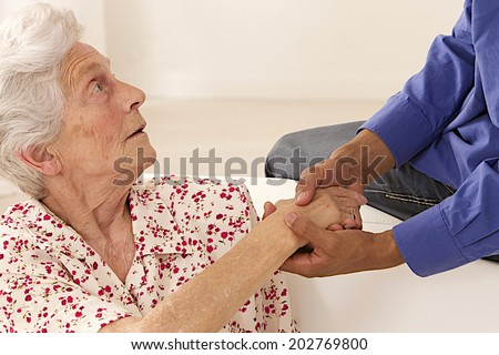 Caregiver holding elderly lady's hands.  - stock photo