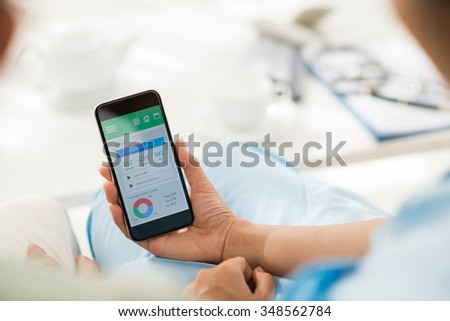 Caregiver showing diet tracker to the patient - stock photo