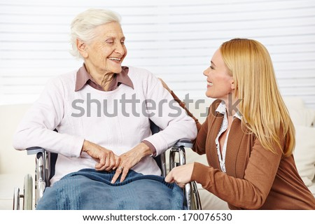 Caregiver woman talking to senior citizen in wheelchair at home - stock photo