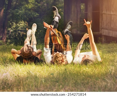 Careless teenagers lying on the green lawn with guitar - stock photo