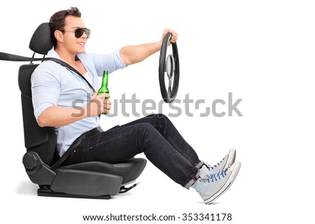 Careless young man driving and holding a bottle of beer isolated on white background - stock photo