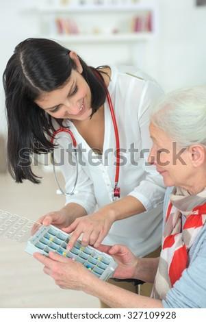 Carer explaining how medication is organised - stock photo