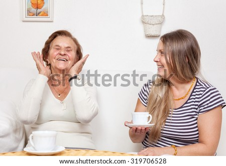 Carer having a cup of tea with an elderly retired woman - stock photo