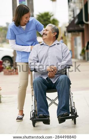 Carer Pushing Disabled Senior Man In Wheelchair - stock photo