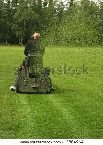 Caretaker mowing a soccer field - stock photo