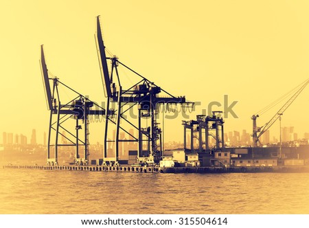 Cargo and transportation industry - cargo shipping and commercial terminal in seaport at sunset. Industrial landscape with gantry cranes in sea port. - stock photo