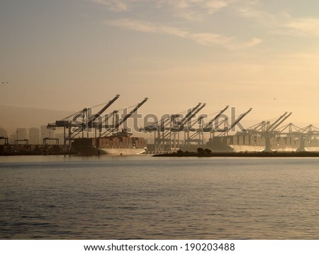 Cargo Boats for of crates rest under cranes in Oakland Harbor on a foggy day in California. - stock photo