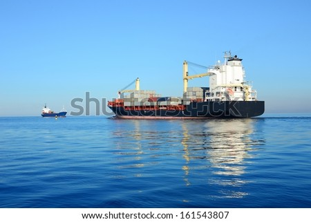 cargo container ship and small cargo ship sailing in still water