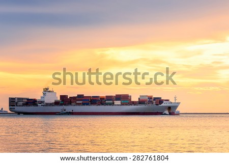 Cargo container ship at mediterranean coast in sunset  - stock photo
