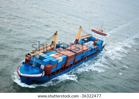 Cargo container ship loaded in channel headed out to sea. - stock photo