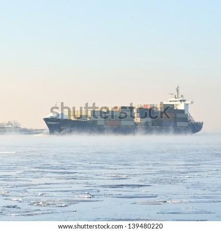 cargo container ship sailing in still frozen winter sea - stock photo