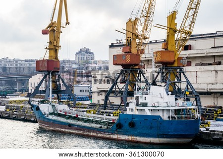 Cargo cranes in the port in the winter and boat