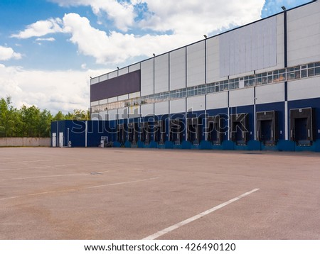 Cargo docks at big industrial warehouse building - stock photo