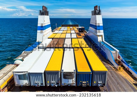 Cargo ferry commercial industrial ship with truck freight containers in the sea - stock photo