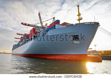 Cargo freight ship with stacked container at harbor terminal - stock photo