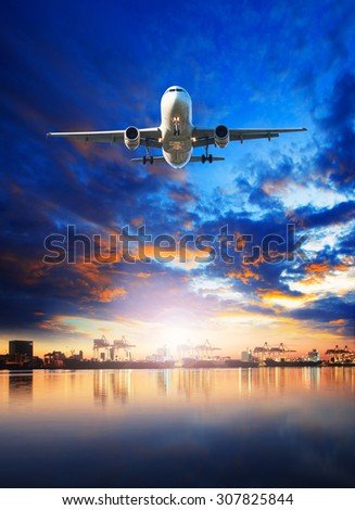 cargo plane flying against blue sky and shipping port behind - stock photo