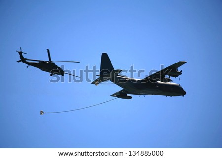 Cargo plane getting refueling in mid air - stock photo