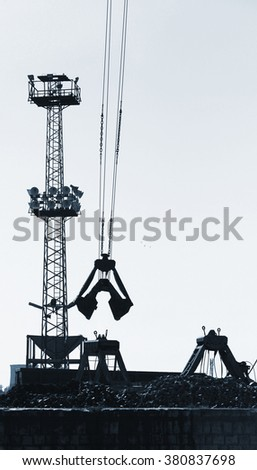 Cargo port fragment with industrial constructions and grapple loader on ropes, vertical monochrome photo - stock photo
