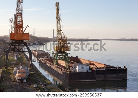 Cargo port of a great river with harbor cranes