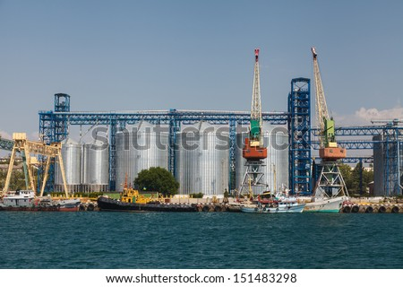 Cargo port with cranes and grain dryers - stock photo